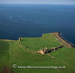 Dunstanburgh Castle lies on a headland on the coast of Northumberland, between the villages of Craster and Embleton, England